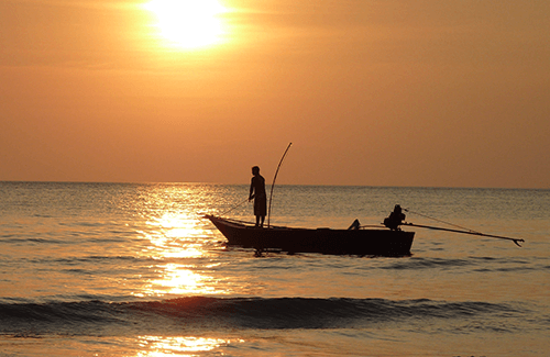 Man fishing from deck of fishing boat on the ocean as the sun sets.